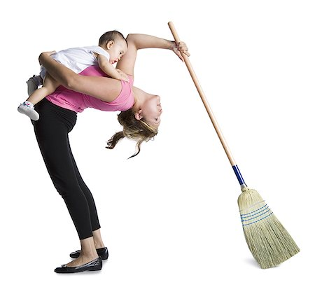 Contortionist mother sweeping while holding baby daughter Stock Photo - Premium Royalty-Free, Code: 640-02768497