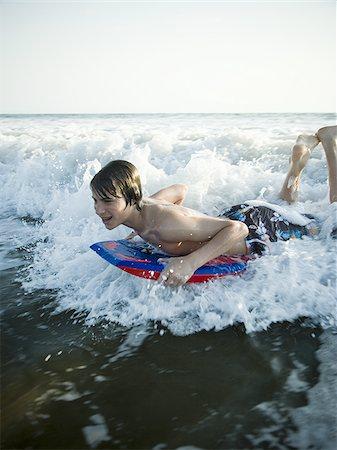 preteen  smile  one  alone - Boy boogie boarding Stock Photo - Premium Royalty-Free, Code: 640-02769185