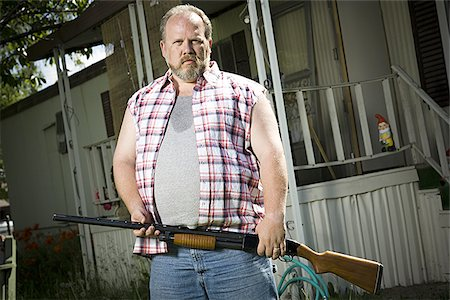 Overweight man with a shotgun Stock Photo - Premium Royalty-Free, Code: 640-02769446
