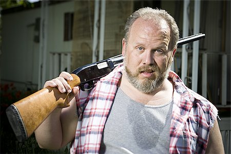 Overweight man with a shotgun Stock Photo - Premium Royalty-Free, Code: 640-02769449