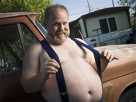 Overweight man with suspenders by truck Stock Photo - Premium Royalty-Free, Code: 640-02769475