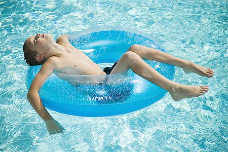 Young boy floating on life ring in swimming pool Stock Photo - Premium Royalty-Free, Code: 640-02769712