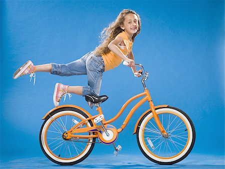 forward - Girl on orange bicycle kneeling on seat with foot up Stock Photo - Premium Royalty-Free, Code: 640-02774428