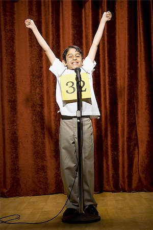 preteen  smile  one  alone - Boy contestant standing at microphone waving and smiling Stock Photo - Premium Royalty-Free, Code: 640-02774525
