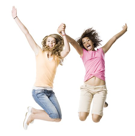 Two girls with braces holding hands and leaping Stock Photo - Premium Royalty-Free, Code: 640-02775298