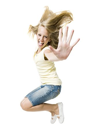 Girl smiling and leaping with hand up Stock Photo - Premium Royalty-Free, Code: 640-02775319