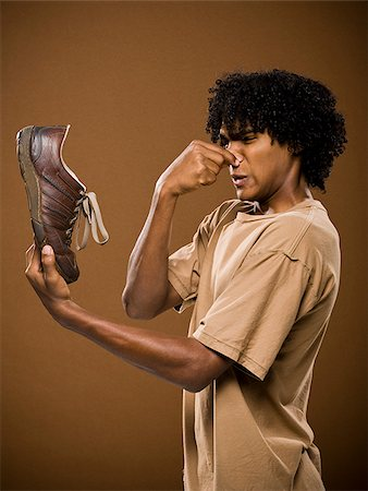 smelly - young man in a brown shirt holding a shoe and his nose. Stock Photo - Premium Royalty-Free, Code: 640-02776875