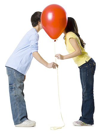 preteen kissing - couple kissing behind a red balloon Stock Photo - Premium Royalty-Free, Code: 640-02778548