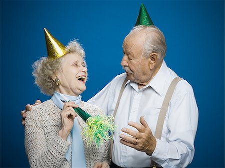 Older couple with noisemakers and party hats Stock Photo - Premium Royalty-Free, Code: 640-02770024