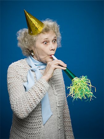 Older woman with noisemaker and party hat Stock Photo - Premium Royalty-Free, Code: 640-02770027