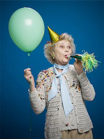 Older woman with noisemaker and party hat Stock Photo - Premium Royalty-Free, Code: 640-02770037