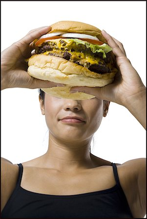 Woman eating a supersized hamburger Stock Photo - Premium Royalty-Free, Code: 640-02770318
