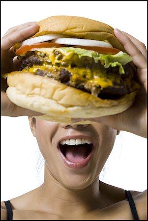 Woman eating a supersized hamburger Stock Photo - Premium Royalty-Free, Code: 640-02770319