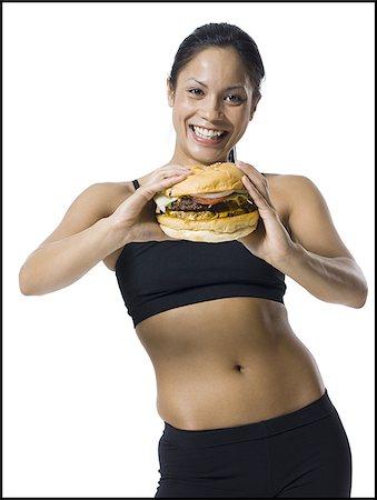 Woman eating a supersized hamburger Stock Photo - Premium Royalty-Free, Code: 640-02770322