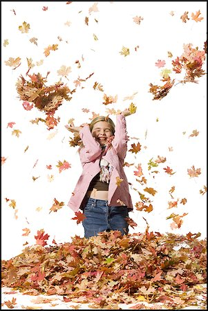 pile leaves playing - Young girl playing in fallen leaves Stock Photo - Premium Royalty-Free, Code: 640-02770474