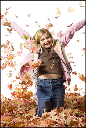 pile leaves playing - Young girl playing in fallen leaves Stock Photo - Premium Royalty-Free, Code: 640-02770476