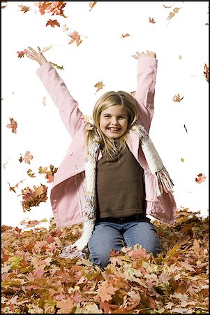 pile leaves playing - Young girl playing in fallen leaves Stock Photo - Premium Royalty-Free, Code: 640-02770477