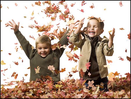 pile leaves playing - Young children playing in pile of fallen leaves Stock Photo - Premium Royalty-Free, Code: 640-02770478