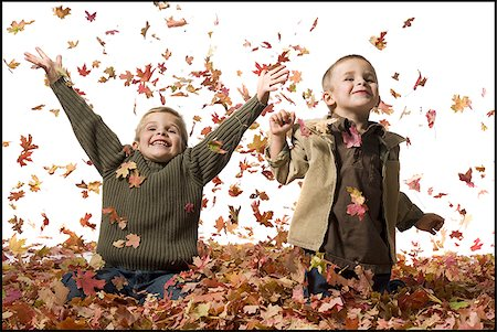pile leaves playing - Young children playing in pile of fallen leaves Stock Photo - Premium Royalty-Free, Code: 640-02770479