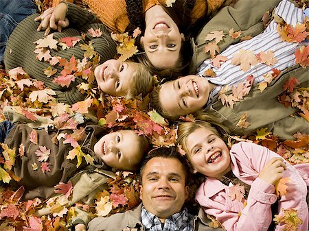 pile leaves playing - Young girls playing in pile of fallen leaves Stock Photo - Premium Royalty-Free, Code: 640-02770480