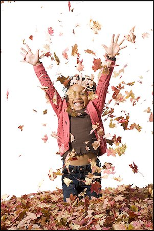 pile leaves playing - Young girl playing in fallen leaves Stock Photo - Premium Royalty-Free, Code: 640-02770514