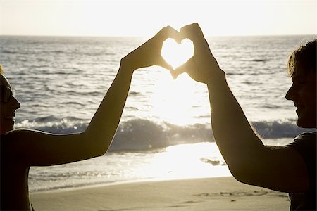 female silhouettes heart - Couple on a beach making a heart symbol with their hands Stock Photo - Premium Royalty-Free, Code: 640-02770726