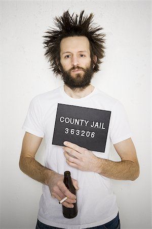 Mug shot of man with cigarette and beer bottle Stock Photo - Premium Royalty-Free, Code: 640-02770998