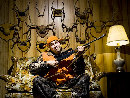 deer hunt - Man on sofa with rifle and antlers Stock Photo - Premium Royalty-Free, Code: 640-02771066