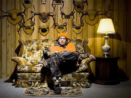 deer hunt - Man on sofa with antlers Stock Photo - Premium Royalty-Free, Code: 640-02771060
