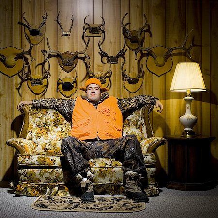 deer hunt - Man on sofa with antlers Stock Photo - Premium Royalty-Free, Code: 640-02771061