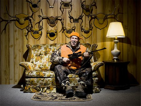 deer hunt - Man on sofa with rifle and antlers Stock Photo - Premium Royalty-Free, Code: 640-02771063