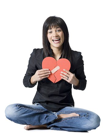female silhouettes heart - Woman sitting cross legged with mended red heart smiling Stock Photo - Premium Royalty-Free, Code: 640-02772772