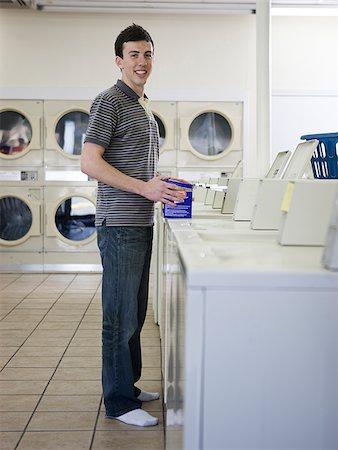 man doing laundry at a laundromat Stock Photo - Premium Royalty-Free, Code: 640-02948166