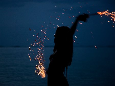 woman holding sparklers on the beach at night Stock Photo - Premium Royalty-Free, Code: 640-02949920