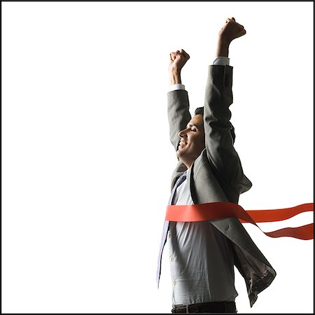 finish line - businessman crossing a finish line of a red ribbon with arms raised in the air triumphantly Stock Photo - Premium Royalty-Free, Code: 640-02952324