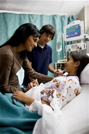 Mother and son talking to girl in hospital bed Stock Photo - Premium Royalty-Free, Code: 640-03255832
