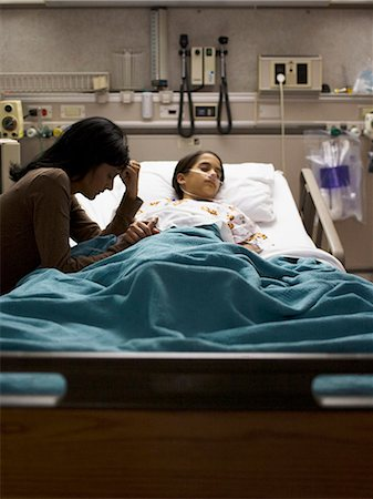 Mother sitting nervously by daughter in hospital bed Stock Photo - Premium Royalty-Free, Code: 640-03255833