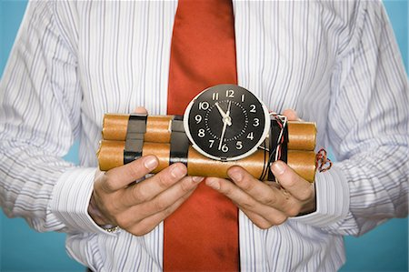 Mid section view of a young man holding a time bomb Stock Photo - Premium Royalty-Free, Code: 640-03256295