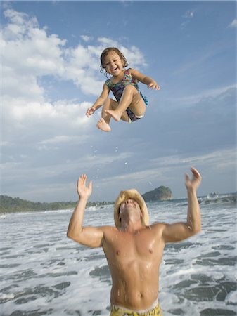 Father tossing his daughter in air Stock Photo - Premium Royalty-Free, Code: 640-03256309