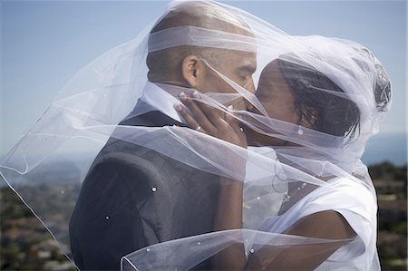 Profile of a newlywed couple kissing each other under a veil Stock Photo - Premium Royalty-Free, Code: 640-03256323