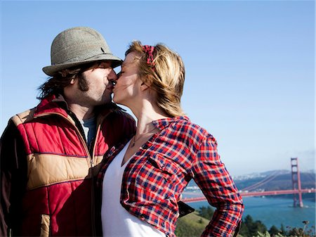 USA, California, San Francisco, young couple kissing, Golden Gate Bridge in background Stock Photo - Premium Royalty-Free, Code: 640-03256921