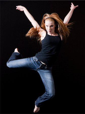 Young woman jumping, studio shot Stock Photo - Premium Royalty-Free, Code: 640-03257310