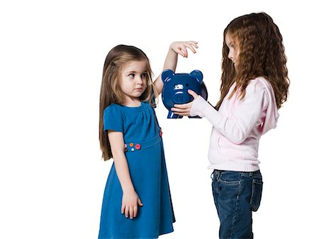 Studio shot of girl (4-5) inserting money to piggy bank held by sister (6-7) Stock Photo - Premium Royalty-Free, Code: 640-03257353