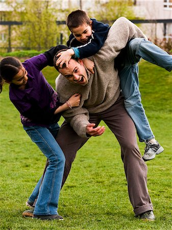 Father play fighting with son and daughter Stock Photo - Premium Royalty-Free, Code: 640-03258621
