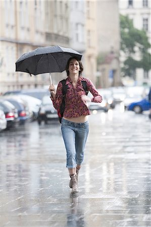 Woman walking down the street in the rain Stock Photo - Premium Royalty-Free, Code: 640-03258653