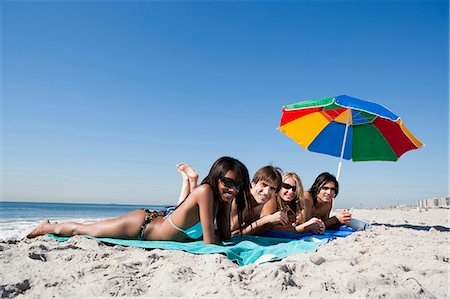 Four adults lying on the beach Stock Photo - Premium Royalty-Free, Code: 640-03258693