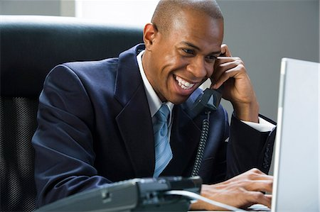 Businessman on laptop and on the phone Stock Photo - Premium Royalty-Free, Code: 640-03259976
