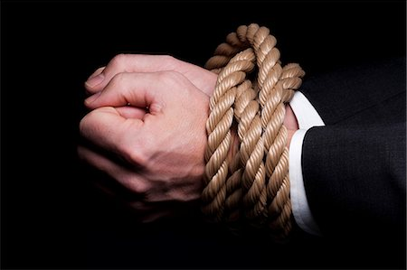 Hands tied at the wrists with rope Stock Photo - Premium Royalty-Free, Code: 640-03264770