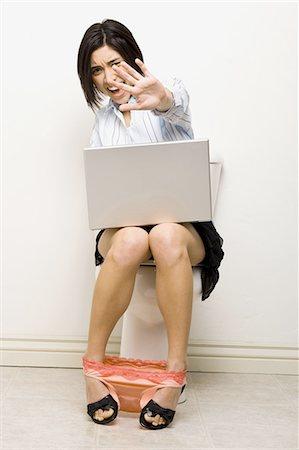 Woman on toilet with laptop Stock Photo - Premium Royalty-Free, Code: 640-03265017