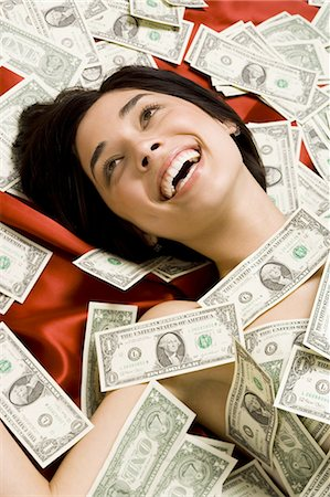 Woman with scattered dollar bills Stock Photo - Premium Royalty-Free, Code: 640-03265032